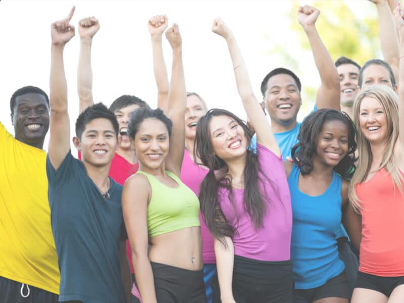 Group of people in exercise clothes with fists in the air